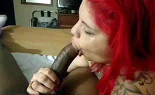 Mulata com cabelo vermelho mamando na grande piroca do negão